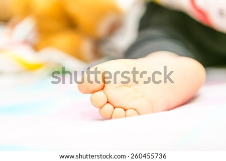 Close up photo of baby foot, photographed when baby is sleeping on bed - stock photo