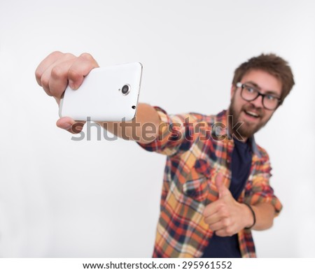 Close-up photo of back side of white smartphone. Bearded man keeping up-to-date mobile phone and showing OK sign for selfie. - stock photo