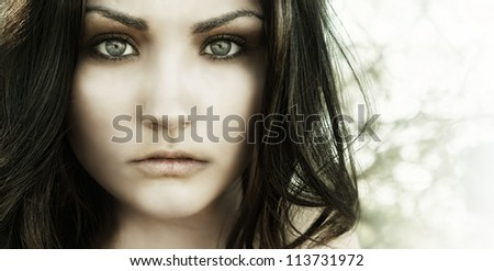 Close up photo of beautiful young woman's face with big eyes and vacant eerie stare. - stock photo