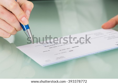 Close-up Photo Of Businesswoman Hand Signing Cheque - stock photo