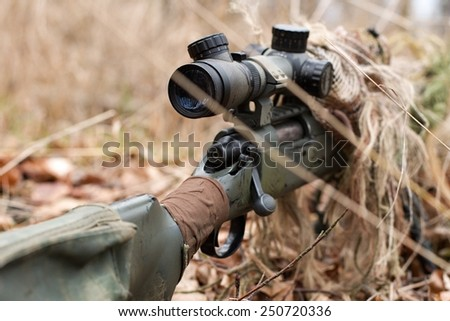 Close-up photo of camouflaged gun on the sniper shooting position - stock photo