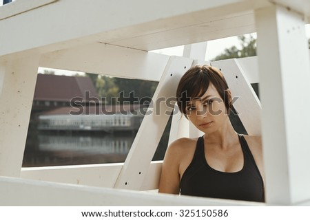 close-up photo of cute brunette in black sport outfit is posing under white wooden judgment seat for beach volleyball on the autumn river beach. She is in leggings, top. Sun is shining. Clouds in sky. - stock photo