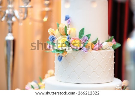 Close up photo of delicious luxury white wedding or birthday cake decorated with cream colorful flowers  - stock photo