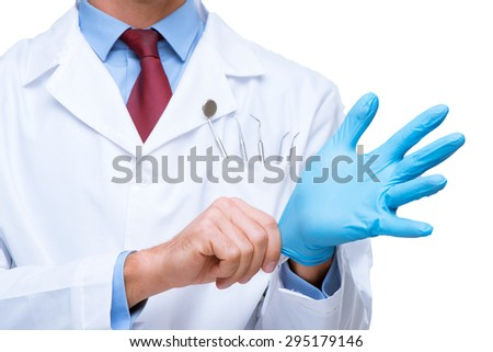 Close up photo of dentist. There are dental instruments and toothbrush in his pocket. He wearing blue glove - stock photo