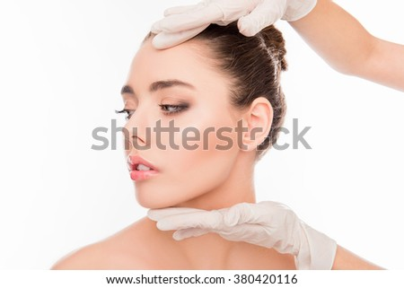 Close up photo of  doctor's hands checking skin before plastic surgery - stock photo