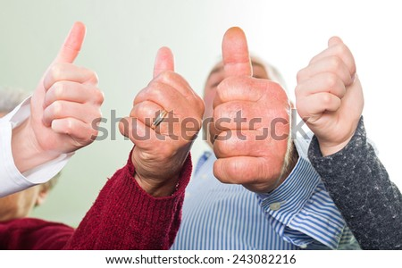 Close up photo of four hands showing thumbs up - stock photo