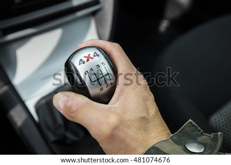 Close-up photo of four-wheel drive vehicle shifter in Finland. The photograph is also a man's hand changing gear.