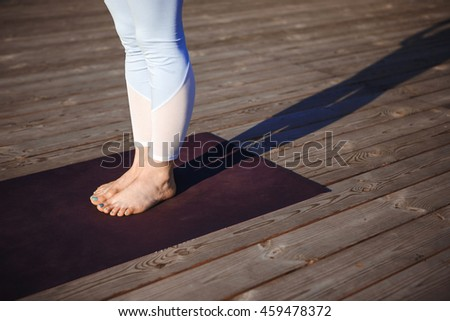 Close up photo of girl's legs over wood background.