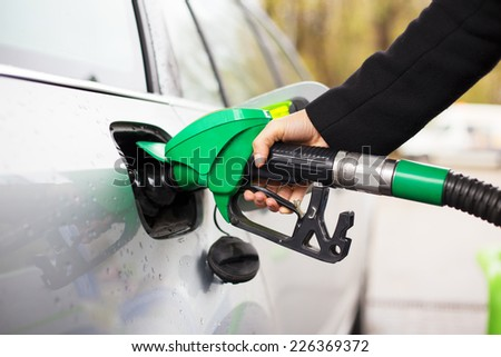 Close-up photo of hand holding fuel pump and refilling car at petrol station - stock photo