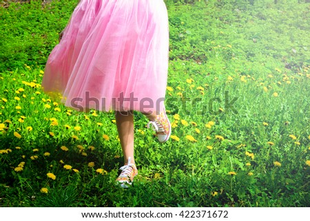 Close up photo of hipster girl legs. Trendy young fashionable sexy woman wearing casual colorful sneakers and light fluffy pink rosy skirt on sunny day outdoors in a forest park with green grass - stock photo