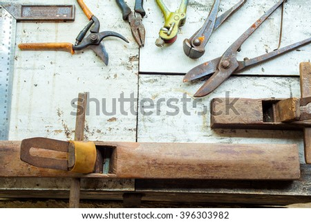 close-up photo of historical carpentry tools on a rough wooden table