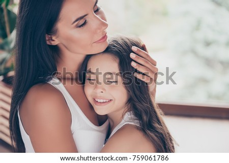Close up photo of hugging smiling mother and daughter, the mother is calming down her little girl after the quarrel