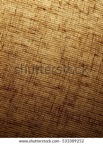close up photo of  lampshade that has light showing through to highlight the shade's fabric texture