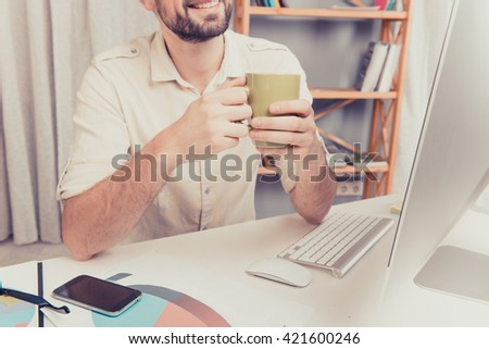 Close up photo of man's hands holding cup with tea