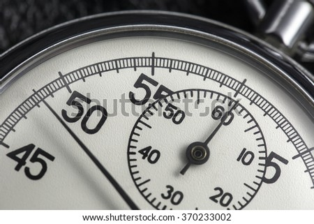 Close-up photo of old analogue stopwatch. It shows a clock face from 45 to 5 seconds. Macro photo. Horizontal.