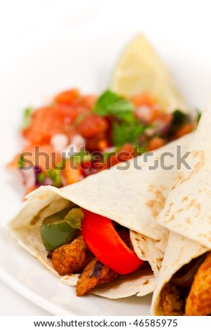 Close-up photo of spicy mexican chicken fajita wraps, with red and green peppers, and fresh tomato salsa and a lime in the background. On a white plate, with a white background.