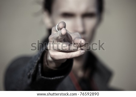 Close-up photo of the criminal man pointing finger. Focus on the fingertip - stock photo