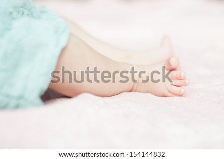 Close up photo of the feet and legs of a young baby