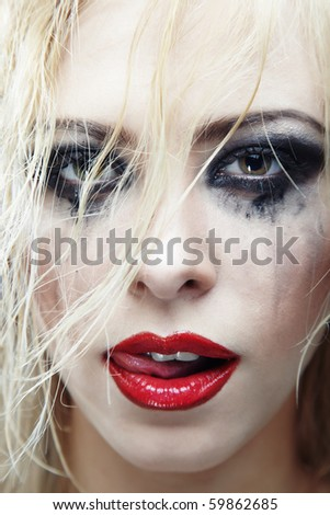 Close-up photo of the woman face with bizarre makeup - stock photo