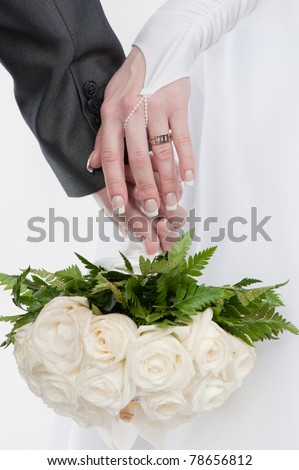 Close up photo of two beautiful hands of the groom and the bride with wedding rings and bouquet of white roses - stock photo