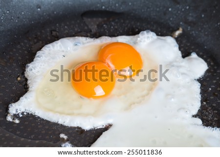 Close-up photo of two scrambled eggs in black frying pan - stock photo