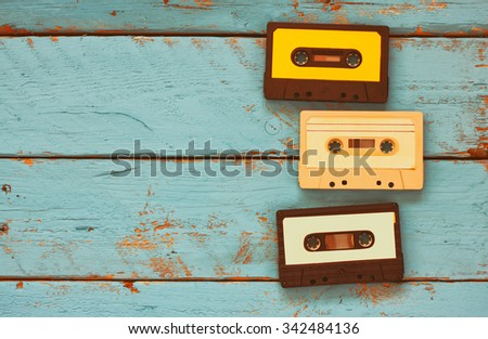 close up photo of vintage cassette tape over aqua wooden table . top view. retro filtered  - stock photo