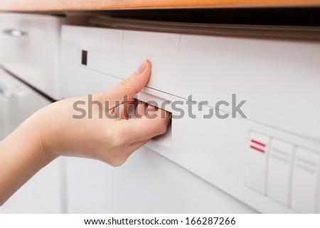 Close-up Photo Of Woman's Hand Opening Dishwasher - stock photo