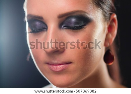 Close up photo of woman with night make up keeping her eyes closed