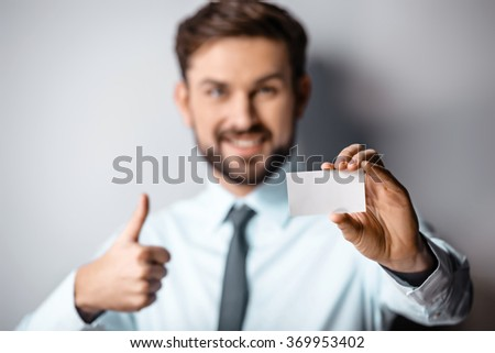 Close up photo of young attractive businessman. Businessman looking at camera, showing thumb up and visit card - stock photo