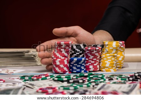 Close up photo of young man hand with poker chips at poker table - stock photo