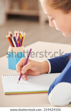 Close up photo of young school girl with pencil writing in her notebook while sitting in school desk - stock photo