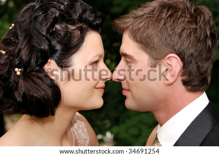 Close-up photo of young wedding couple. They are looking at each other and slightly touching with noses.