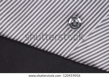 Close-up photograph of a black button on a striped gray pattern. - stock photo
