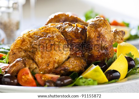Close up photograph of a grilled chicken with tomato and olives