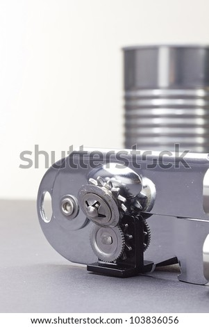 Close-up photograph of a metal can opener next to a metal can. - stock photo