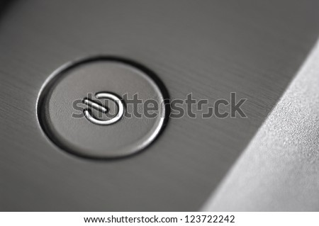 close up photograph of a silver laptop power button - stock photo