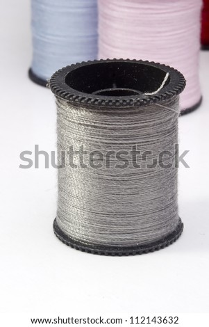 Close-up photograph of a silver spool of thread. - stock photo