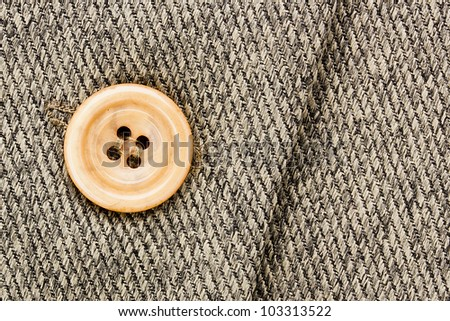 Close-up photograph of an orange button on gray fabric. Add your text to the background. - stock photo