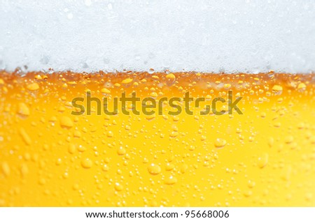 Close-up picture of a beer with bubbles and its foam. - stock photo