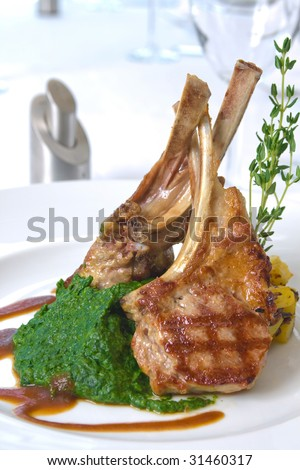 Close up picture of a roasted lamb chop and vegetables on white background