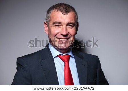 Close up picture of a smiling middle aged business man looking at the camera.