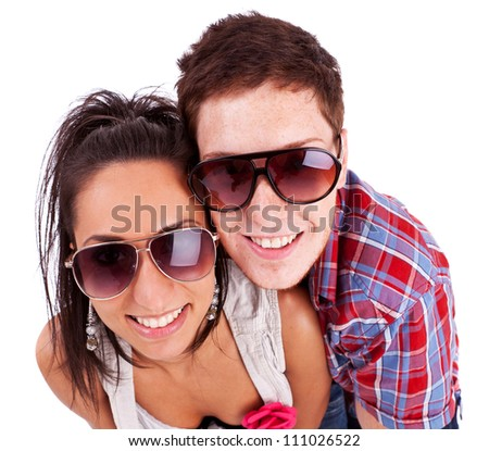 Close-up picture of a young couple wearing sunglasses and smiling at the camera. Isolated on white - stock photo