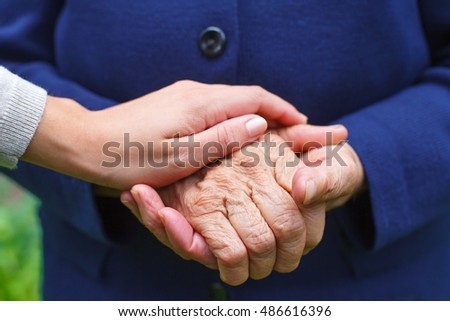Close-up picture of an elderly woman's hands with her grandchild