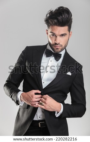 Close up picture of an elegant man in tuxedo closing his jacket while looking away from the camera. - stock photo