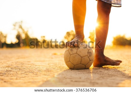 Close up picture of an old ball and foot of a boy who is playing football in the sunshine day. - stock photo