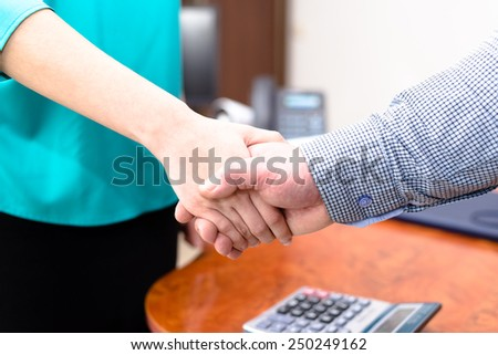 Close up picture of business man and woman shaking hands in office - stock photo