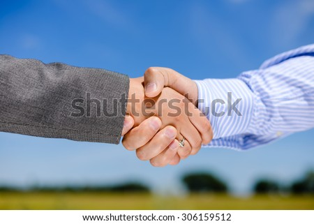 Close-up picture of business people handshaking on sunny day outdoors background - stock photo