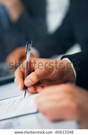 Close-up picture of businessman's hand writing in the document