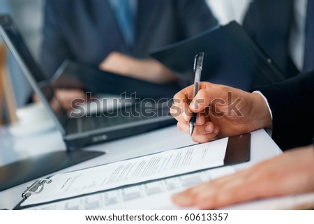 Close-up picture of businessman's hands with pen and documents - stock photo