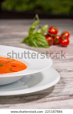 Close-up picture of cold tasty tomato soup gazpacho with species on the wooden table in vegan caffee with tomatoes standing near a plate, with copy place and selective focus on a half of the plate - stock photo